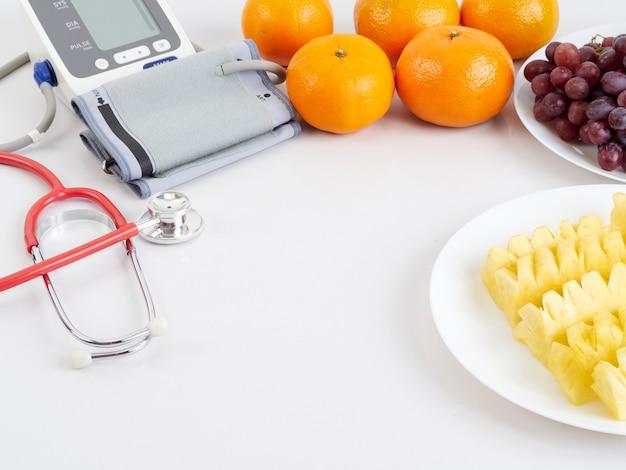 Estetoscópio e monitor automático de pressão arterial com frutas