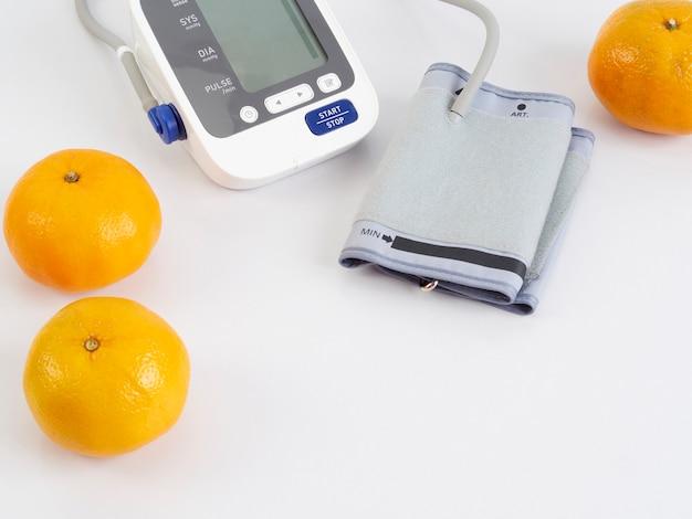 Estetoscópio e monitor automático de pressão arterial com laranjas