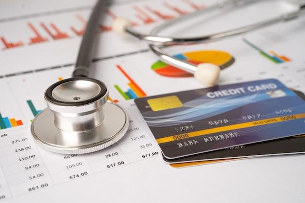 Estetoscópio e notas de dólar americano em gráfico ou papel milimetrado, financeiro, conta, estatísticas e conceito de saúde médica de dados de negócios.