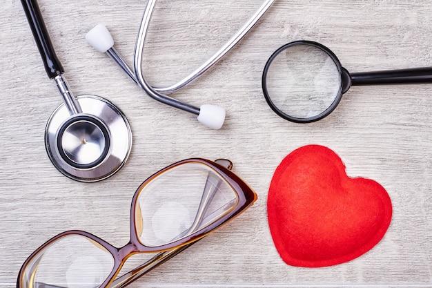 Estetoscópio e óculos. coração e lupa de tecido vermelho.