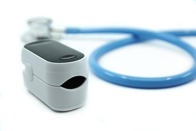 Estetoscópio e oxímetro de pulso isolados no fundo branco covid19 conceito de saúde