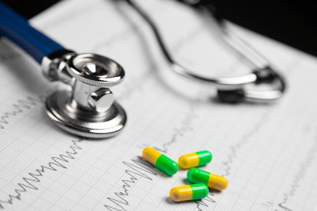Estetoscópio e pílulas coloridas deitado na folha com o eletrocardiograma