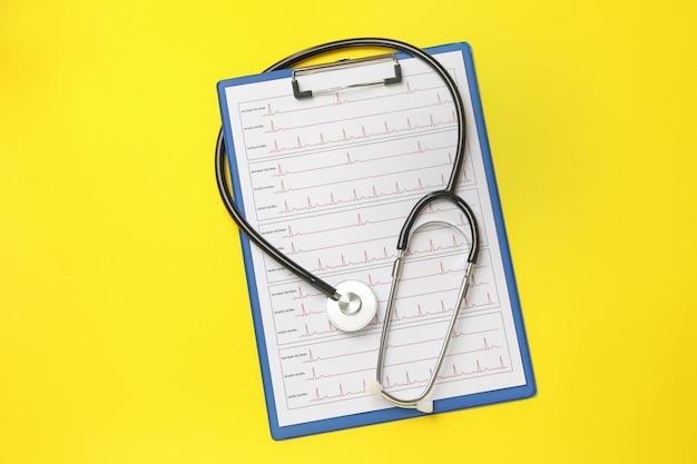 Estetoscópio e prancheta com eletrocardiograma em amarelo