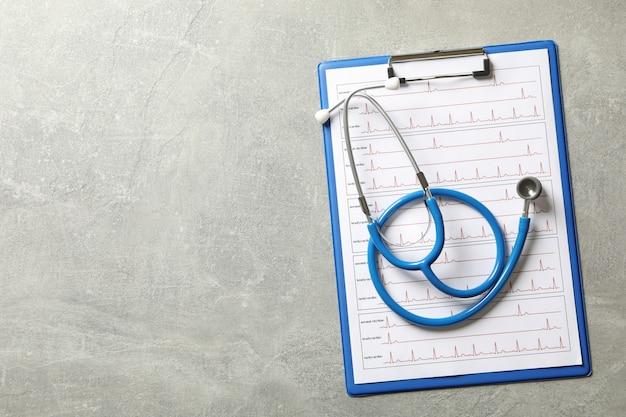 Estetoscópio e prancheta com eletrocardiograma em cinza