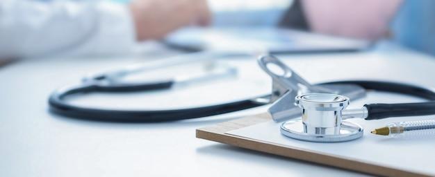 Estetoscópio e prancheta no local de trabalho do médico fecham