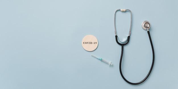 Estetoscópio e seringa médica ao lado de um sinal covid 19