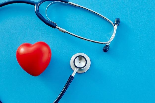 Estetoscópio e um coração vermelho em um fundo azul
