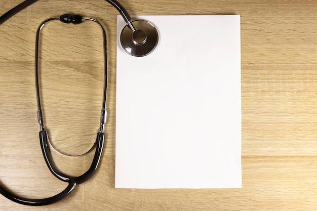 Estetoscópio e um pedaço de papel em um fundo de madeira com espaço de cópia para o seu texto. conceito de cuidados de saúde. equipamentos de saúde e médicos. check-up médico e diagnóstico. deveres dos médicos.