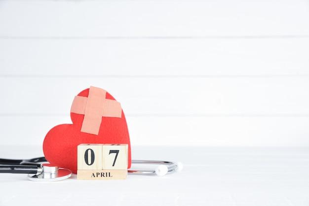 Estetoscópio e vermelho coração com calendário de bloco de madeira de 7 de abril de texto sobre fundo branco de madeira.