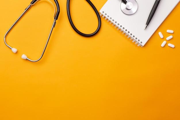 Estetoscópio, em, doutores, escrivaninha, com, caderno, e, pílulas, vista superior