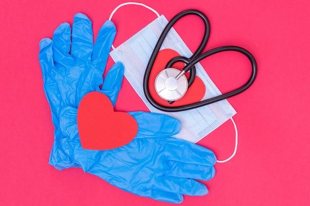 Estetoscópio em forma de coração negro na máscara protetora médica e luvas médicas azuis e coração de papel vermelho
