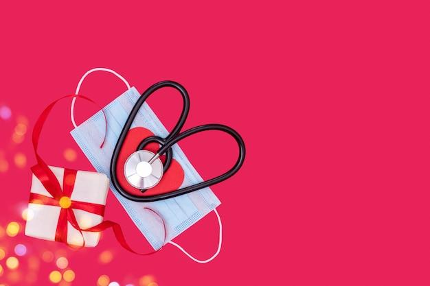Estetoscópio em forma de coração preto em máscara de proteção médica e caixa de presente branca