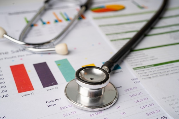 Estetoscópio em gráficos e papel gráfico, finanças, conta, estatísticas, investimento, economia de dados de pesquisa analítica e conceito de empresa de negócios.