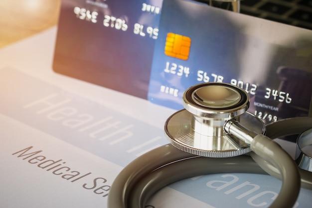 Estetoscópio em mock up cartão de crédito com número no titular do cartão na mesa do hospital. ins de saúde