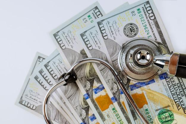 Estetoscópio em notas de dólar americano em despesas médicas, pagamento de cuidados de saúde de medicamentos pagos.
