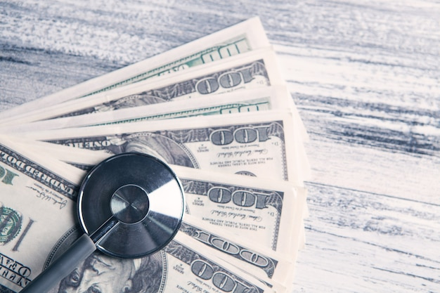 Estetoscópio em notas de dólar em cima da mesa