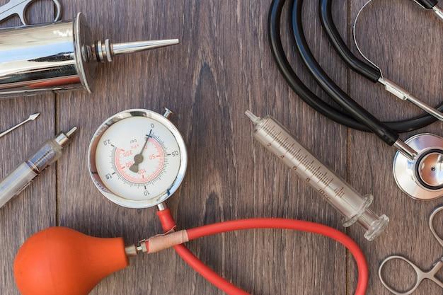 Estetoscópio; esfigmomanômetro e equipamentos médicos na mesa de madeira