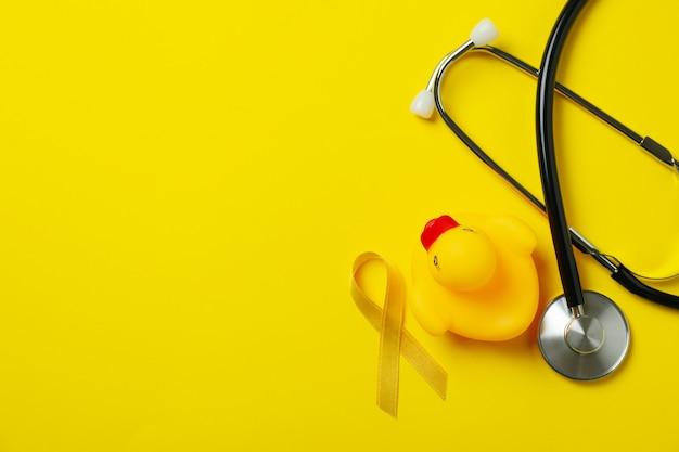 Estetoscópio, fita de conscientização do câncer infantil e pato de borracha em fundo amarelo