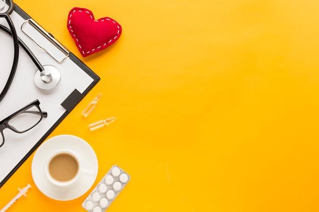 Estetoscópio; forma de coração costurada; xícara de café; medicamento embalado em blister; injeção sobre o pano de fundo amarelo