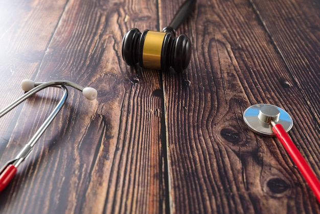 Estetoscópio, livros, pílulas e martelo de juiz, visto de cima.