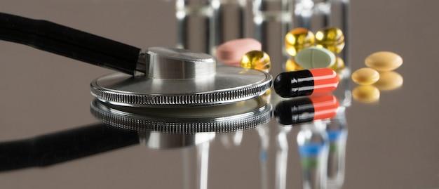 Estetoscópio médico com comprimidos e ampolas em um fundo de espelho com reflexo