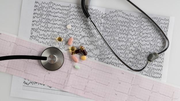Estetoscópio médico com comprimidos e eletrocardiograma sobre um fundo claro. vista do topo