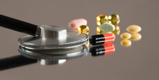 Estetoscópio médico com comprimidos em um fundo de espelho com reflexo