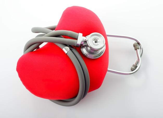 Estetoscópio médico com coração vermelho isolado no branco