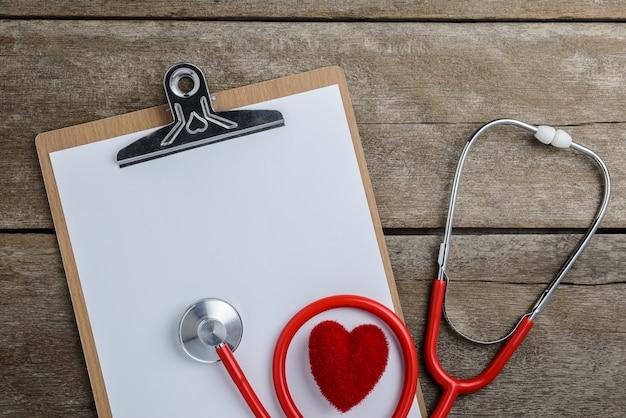 Estetoscópio médico com prancheta e coração na mesa de madeira