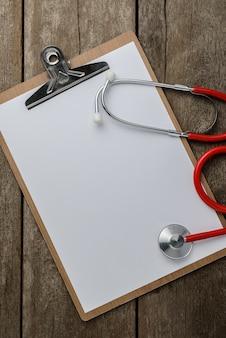 Estetoscópio médico com prancheta na mesa de madeira