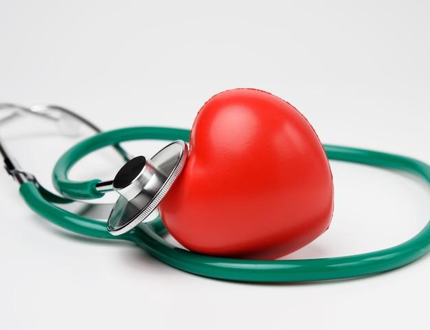 Estetoscópio médico e coração de borracha vermelha em fundo branco, close-up