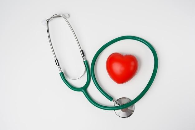 Estetoscópio médico e coração de borracha vermelha na superfície branca, close-up