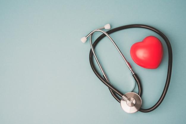 Estetoscópio médico e coração de borracha vermelho sobre fundo azul, vista superior