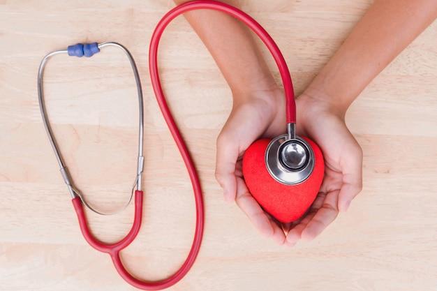 Estetoscópio médico e coração e mão no fundo da tabela
