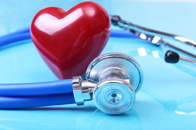Estetoscópio médico e coração vermelho isolado no fundo azul do espelho