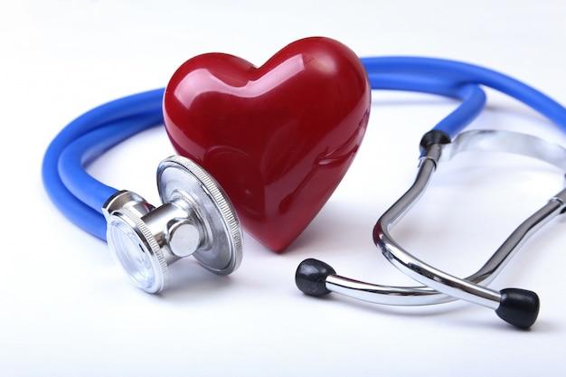 Estetoscópio médico e coração vermelho isolados no fundo branco.