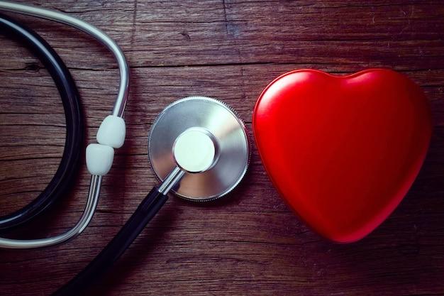 Estetoscópio médico e coração vermelho na mesa de madeira