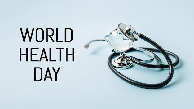 Estetoscópio médico e de saúde do dia mundial da saúde e vidro global no espaço da cópia de fundo azul