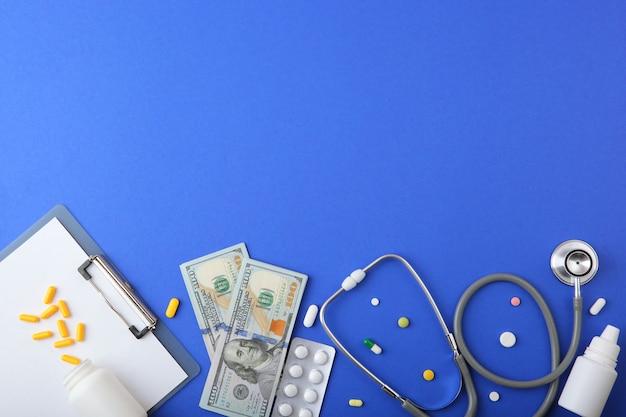 Estetoscópio médico e dinheiro em plano de fundo colorido vista superior