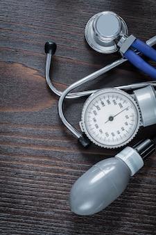 Estetoscópio médico e monitor de pressão arterial no conceito de medicina de fundo de madeira vintage
