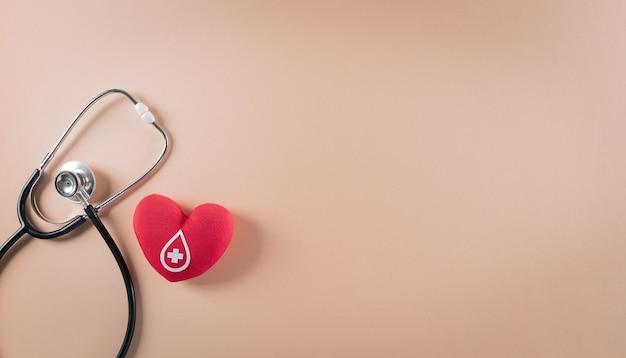 Estetoscópio médico e um coração vermelho feito à mão com um sinal ou símbolo de doação de sangue