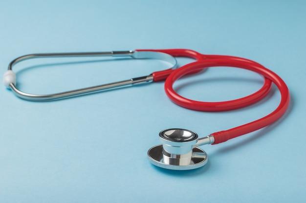 Estetoscópio médico em vermelho sobre um fundo azul. o conceito de tratamento de várias doenças.