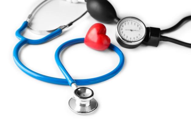 Estetoscópio médico, esfigmomanômetro e coração vermelho. conceito de cardiologia