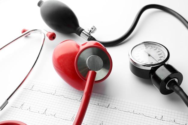 Estetoscópio médico, esfigmomanômetro, eletrocardiograma e coração vermelho. conceito de cardiologia