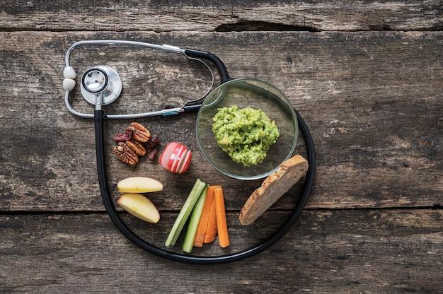 Estetoscópio médico fazendo um loop em torno de um lanche vegan saudável