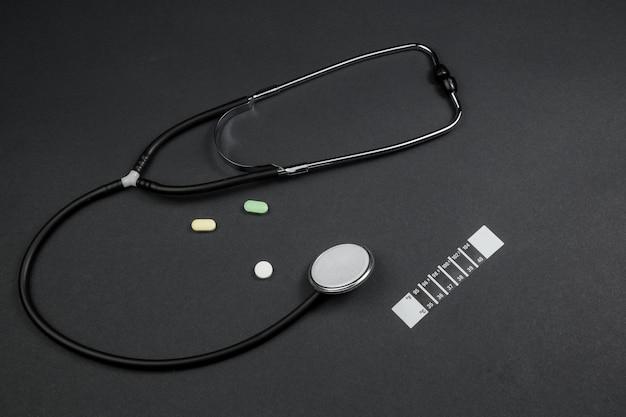 Estetoscópio médico, medicação e tira termômetro em fundo preto isolado