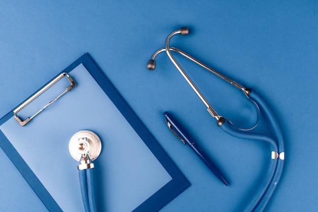 Estetoscópio médico na vista superior de mesa azul clássico