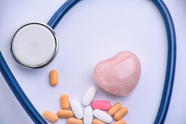 Estetoscópio médico, pílulas e coração de vidro rosa na superfície branca. conceito de cardiologia