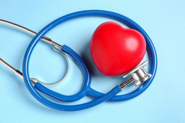 Estetoscópio moderno e coração vermelho na superfície colorida