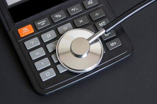 Estetoscópio na calculadora, representando os custos de saúde